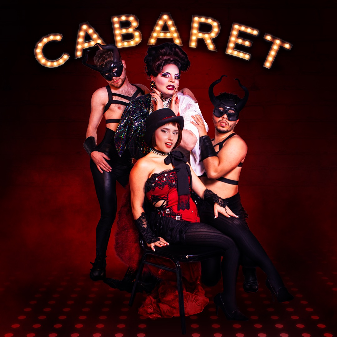 Cabaret sign in marquee lights hangs above four performers, two dressed as scantily clad fawns, one in drag, and one in corset and tights